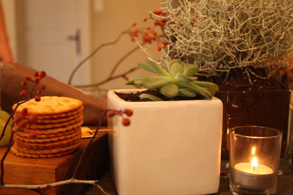 Candles and plants interspersed with the food